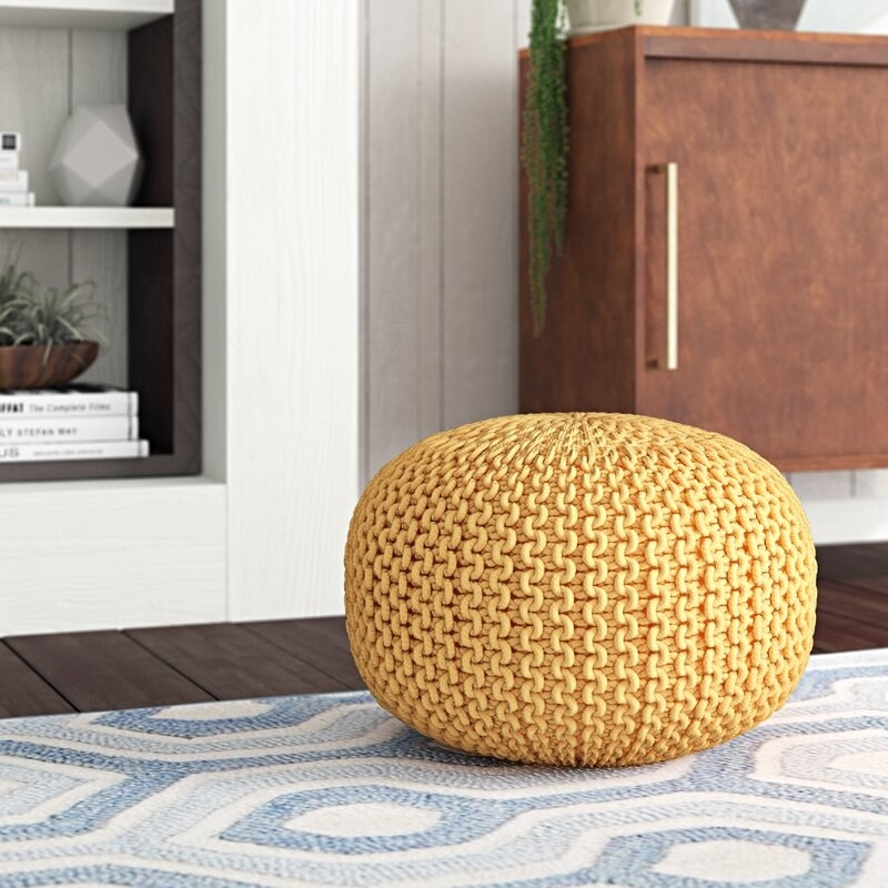 yellow round textured poof on the floor