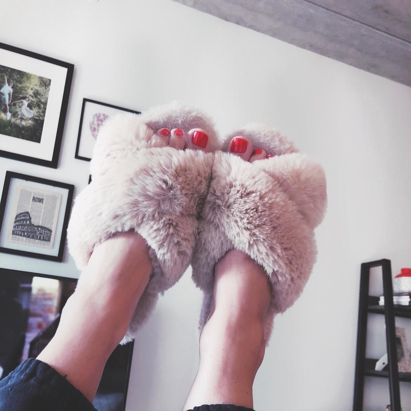 Reviewer pic of their feet in the air with the fuzzy slippers on with a criss-cross over the top of the foot and an open-toe style in light pink