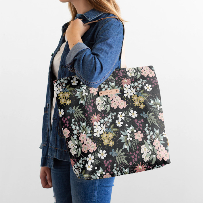 Model with the black tote bag with white, pink, and green floral pattern all of it with a small rectangle name tag in the top middle