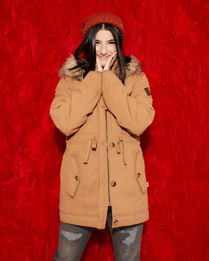 Charli poses in a biege hooded parka