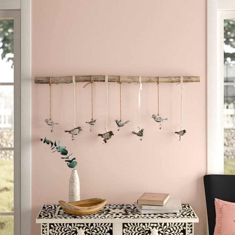 The branch hung up on the wall with eight birds hanging off