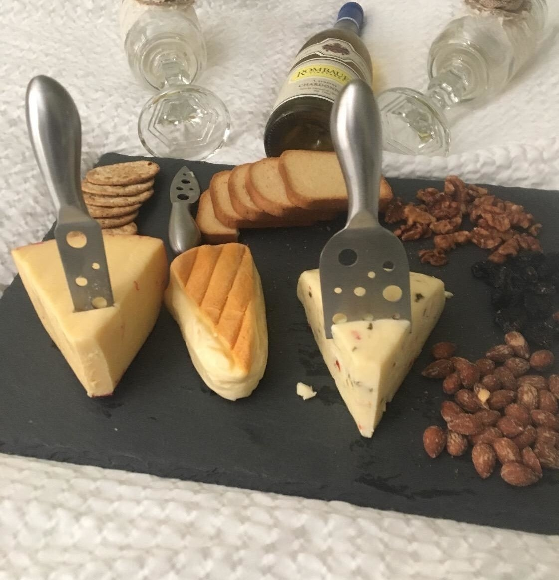 Reviewer pic of the black slate rectangle-shaped board  with a variety of cheese, crackers, and nuts on it with silver tools suck into the cheese