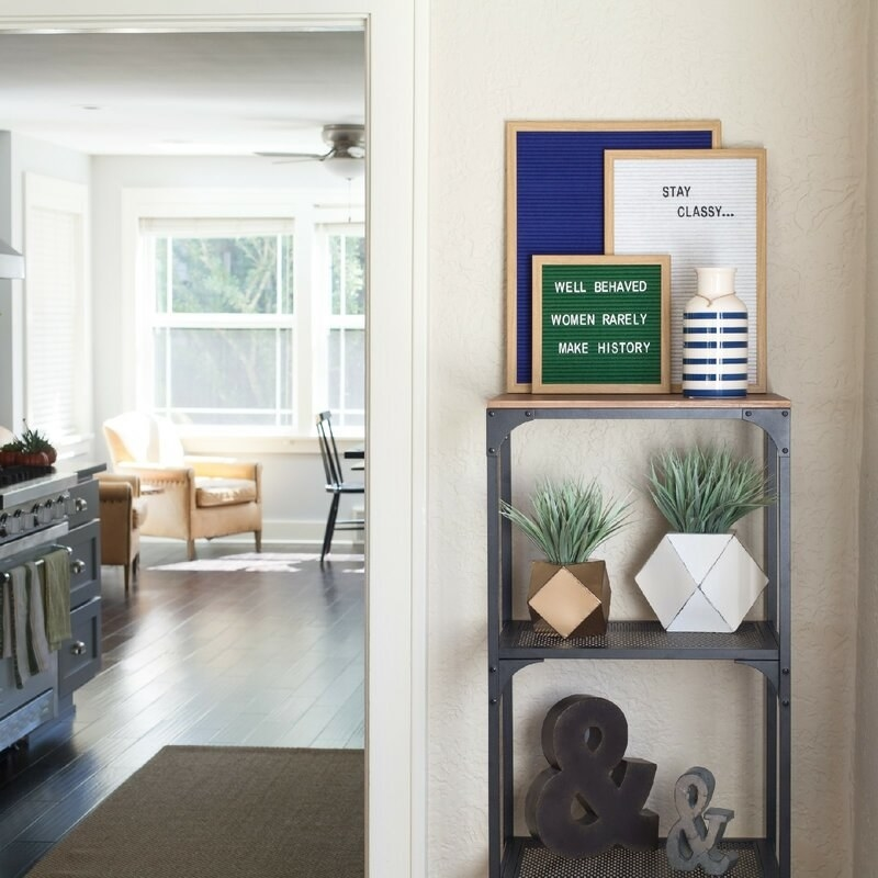Three felt boards on a shelf in a living space