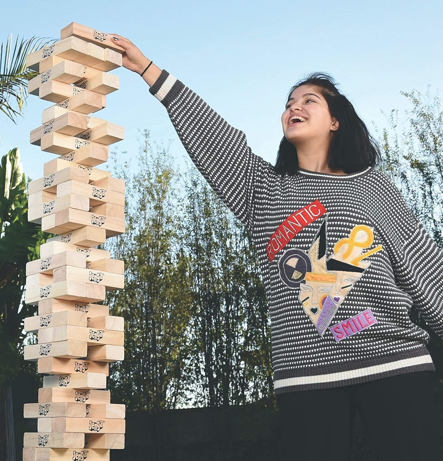 A teenager taking a block off of the Jenga tower