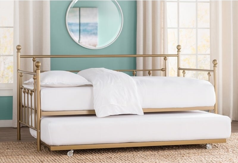 gold bed in room with metal frame