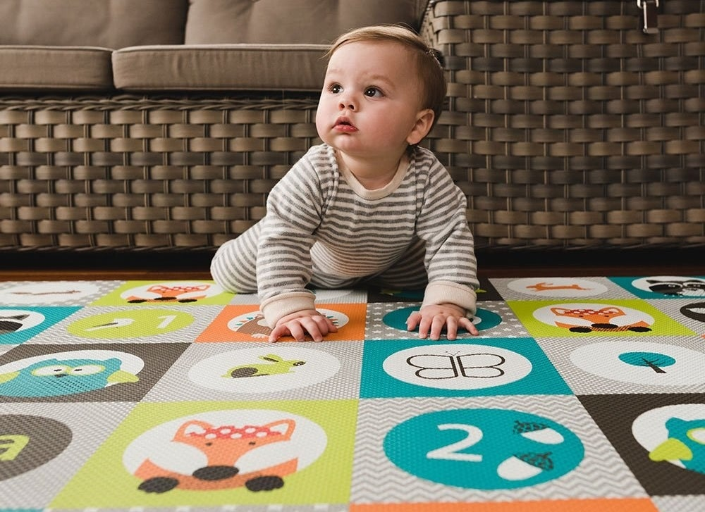 Baby model crawling on a multi-colored play mat