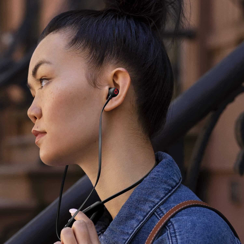 Model wearing black Beats in-ear headphones