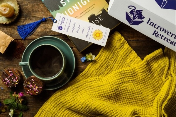 a blanket, chocolates, warm beverage, novel, and other items from the box
