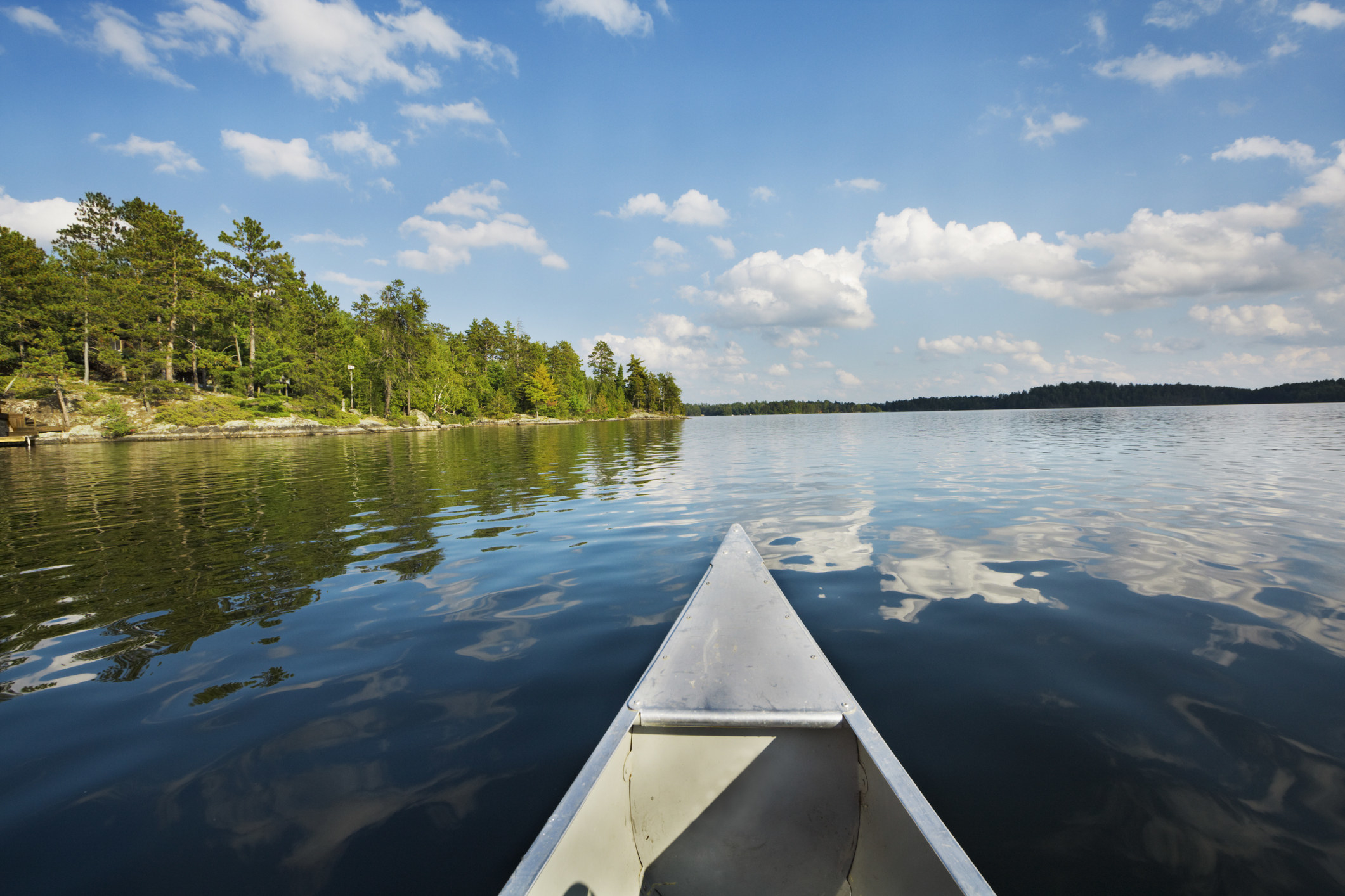 A POV shot of a canoe floating across water with a tree-lined island to the left and a blue sky above