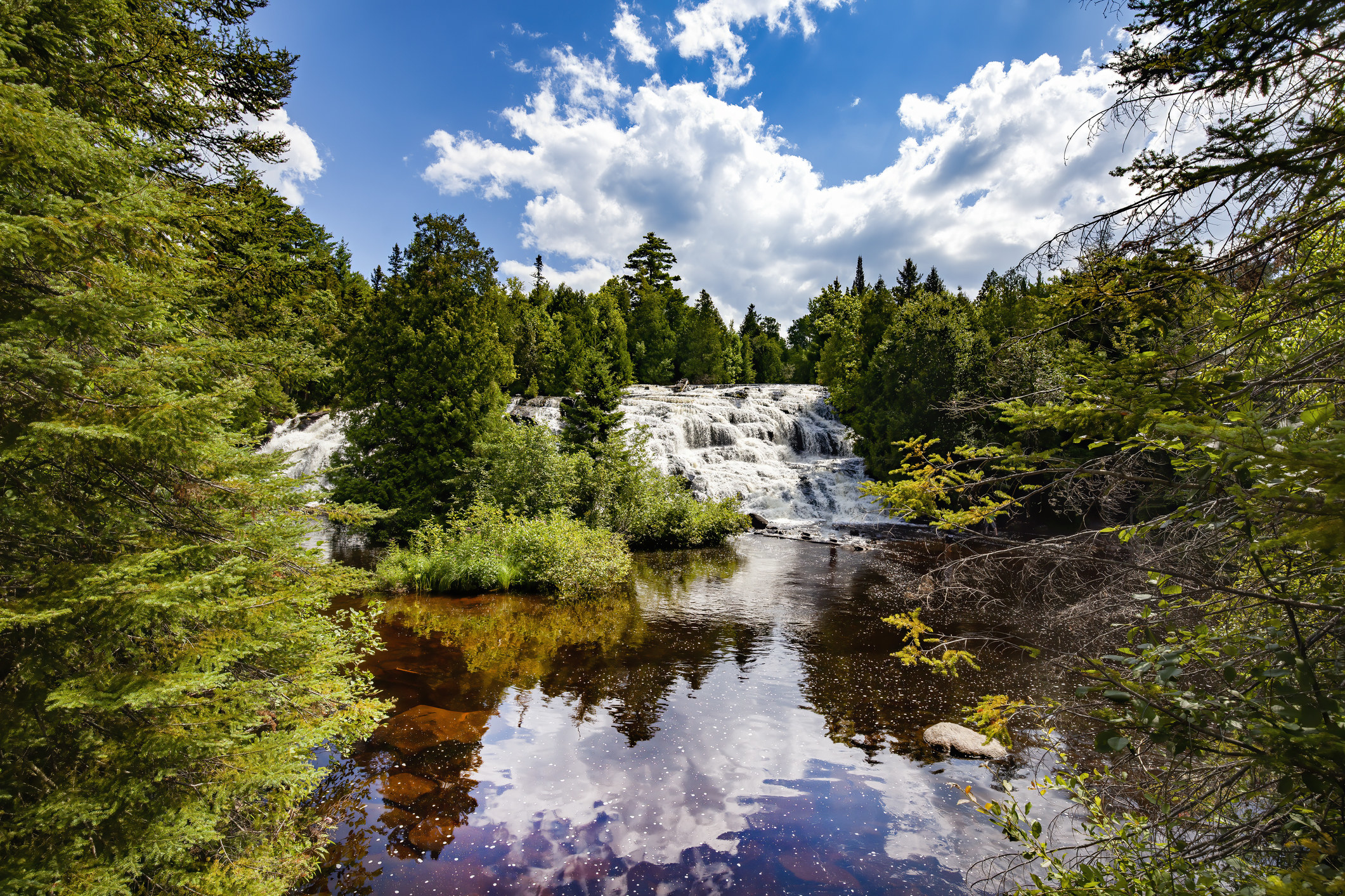 A blue sky with a few fluffy clouds over Bond Falls, which feeds into a still lake and plenty of green trees