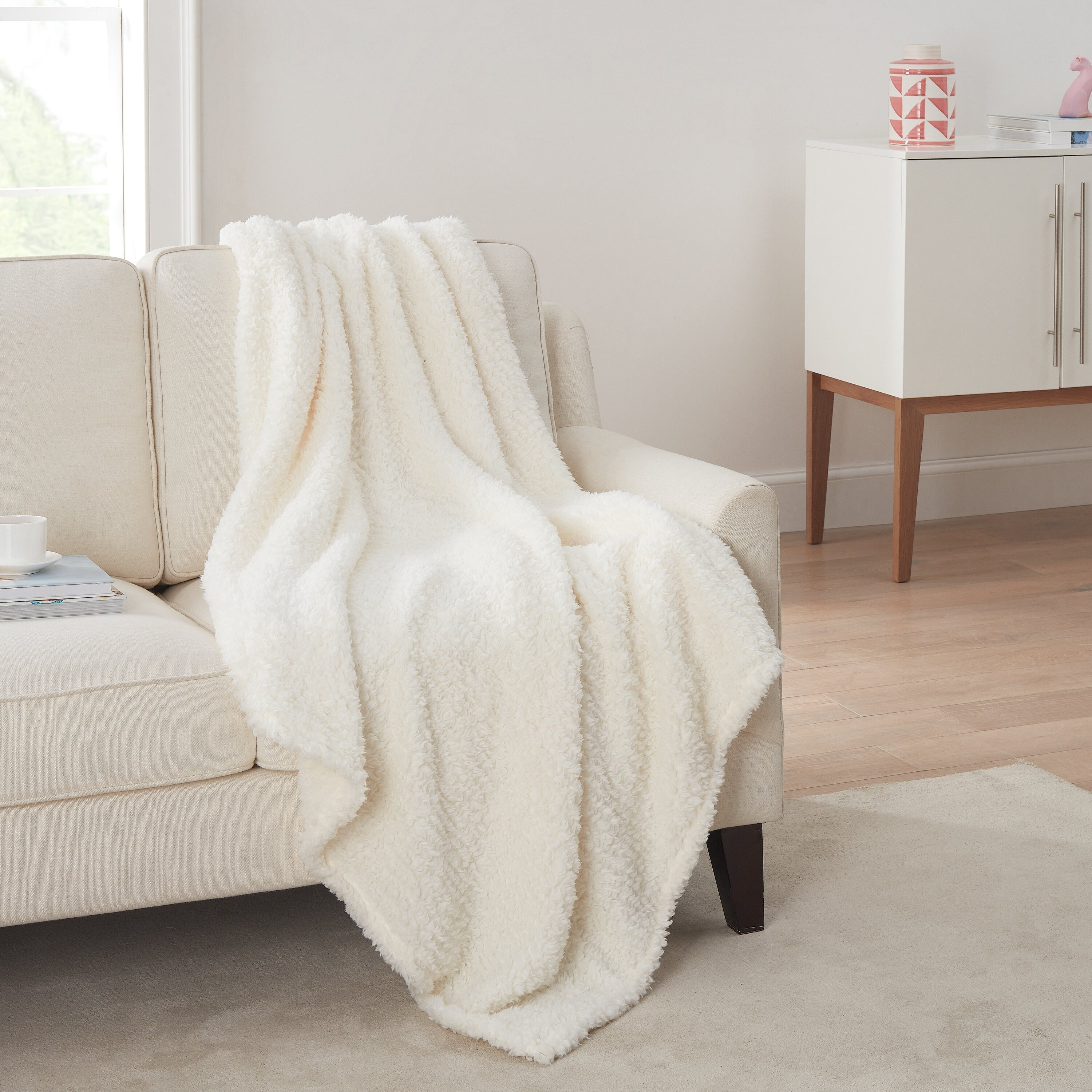 The sherpa fleece throw blanket in cream draped over a couch