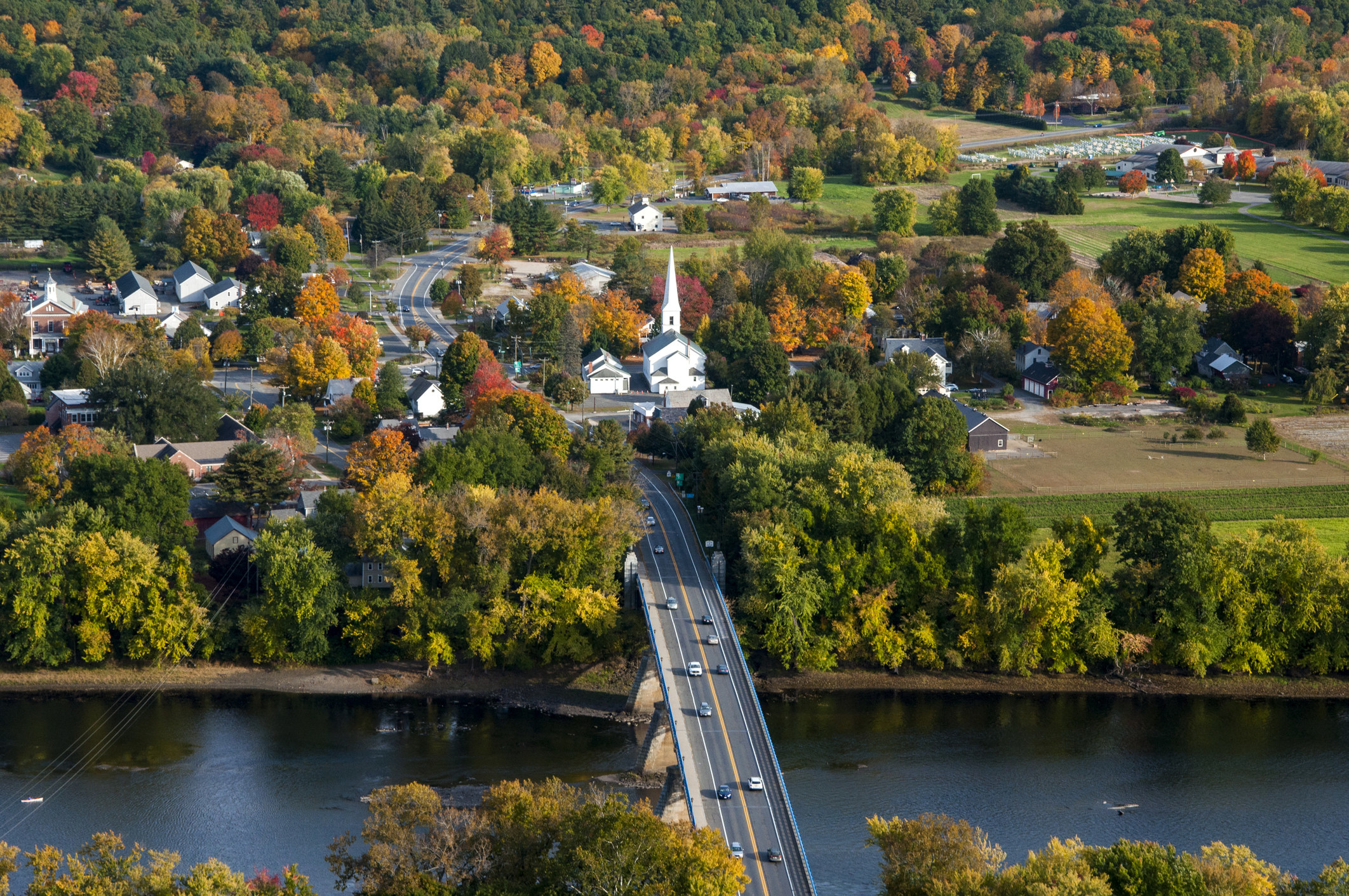 A drone shot of Mount Sugarloaf State Reservation with a bridge over the water and fall foliage beyond