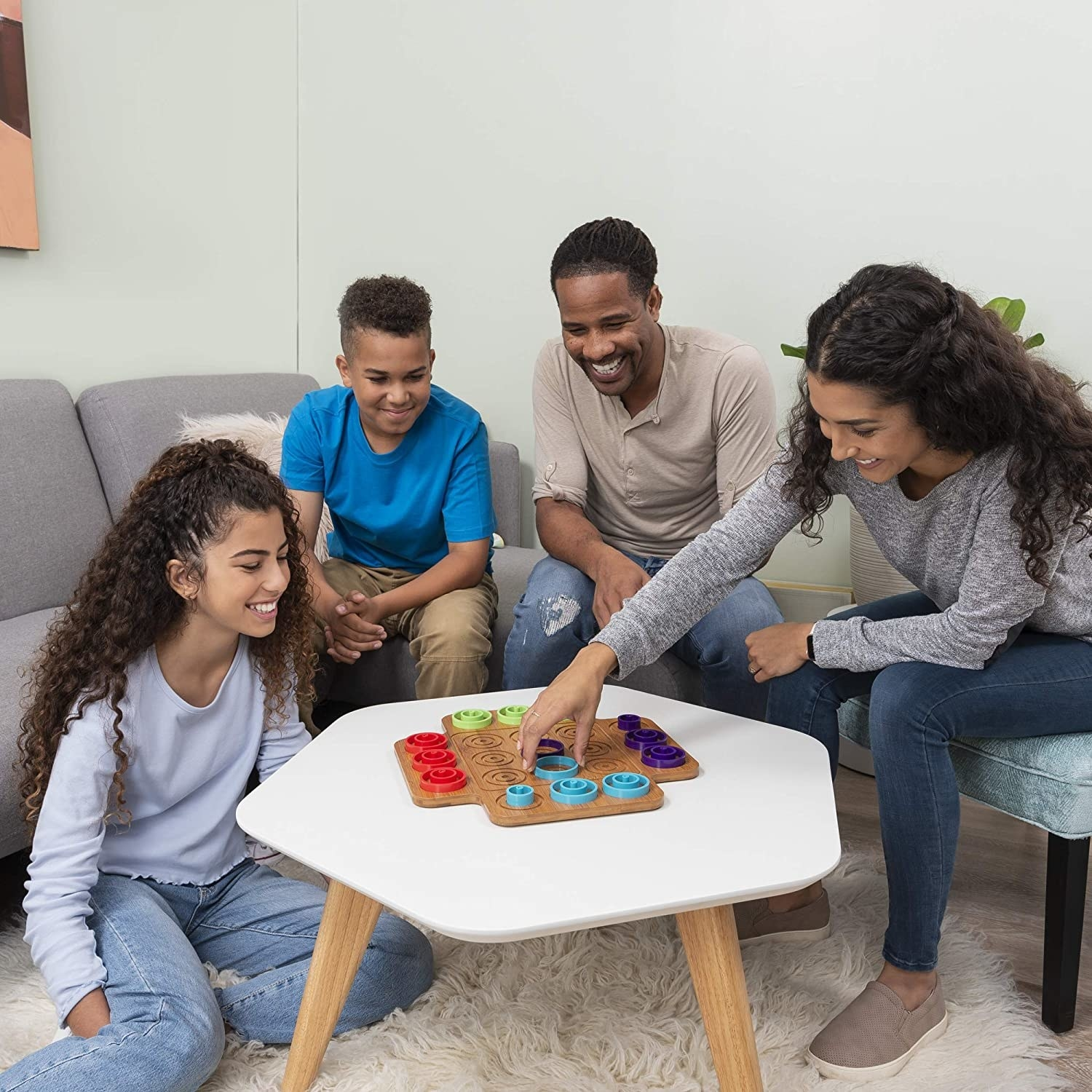 A family of four sitting around a small table with the wood square-shaped board and rings of different sizes and colors around the outside