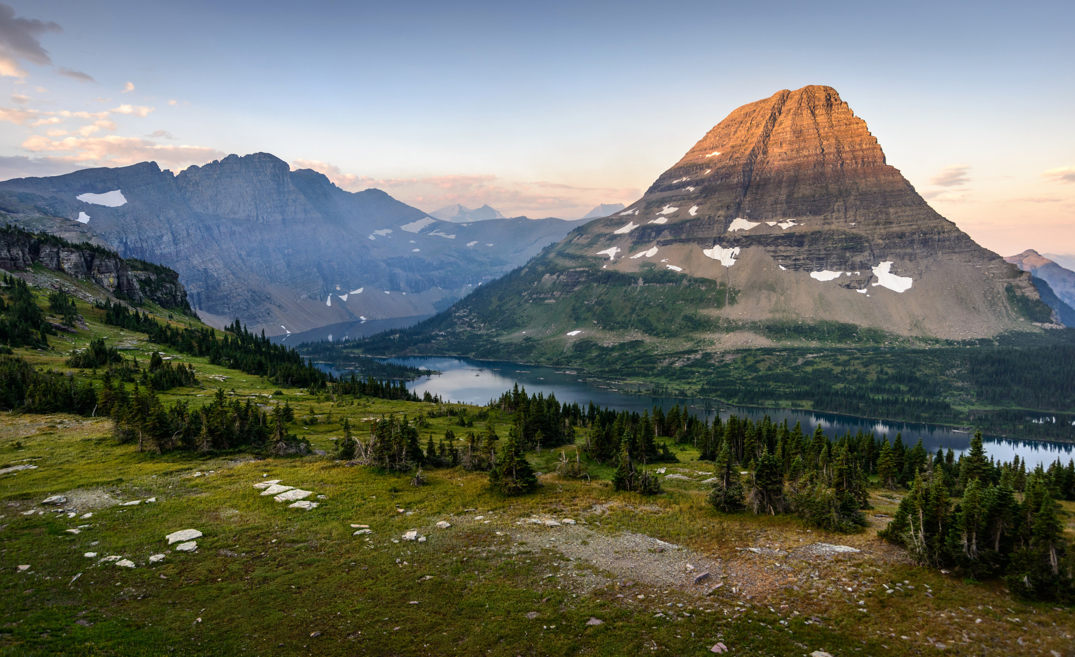 A wide shot of a cliff dotted with trees overlooking a lake and a tall mountain in Glacier National Park
