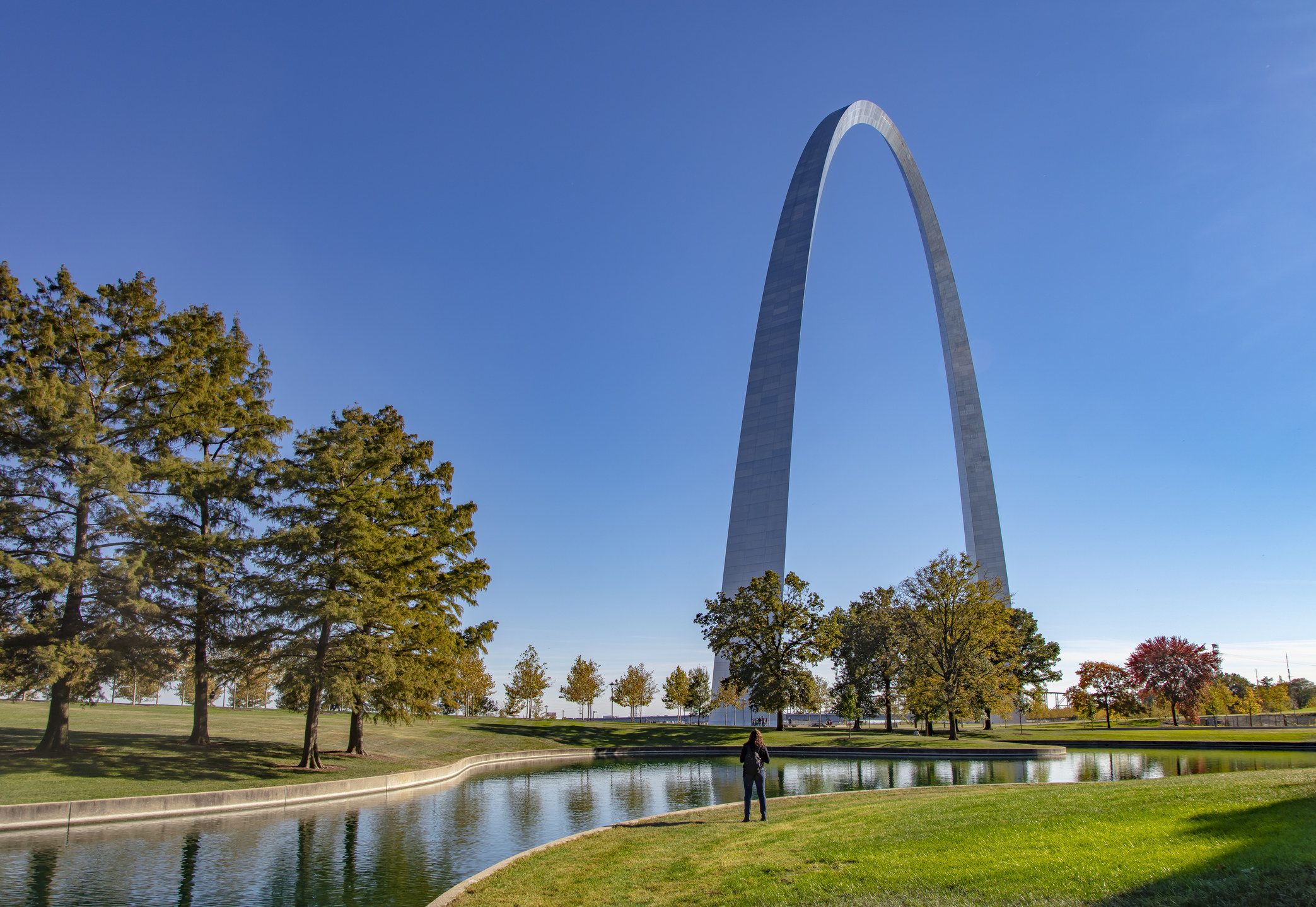 The gateway arch against a cloudless blue sky with grass and trees in the foreground