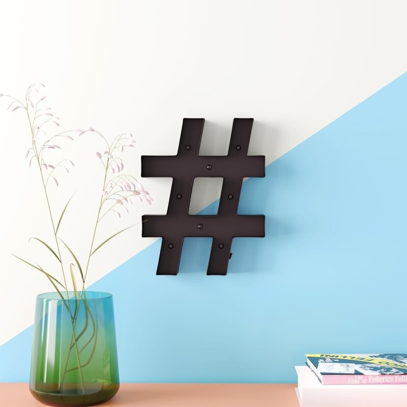 A black LED hashtag mounted on the wall
