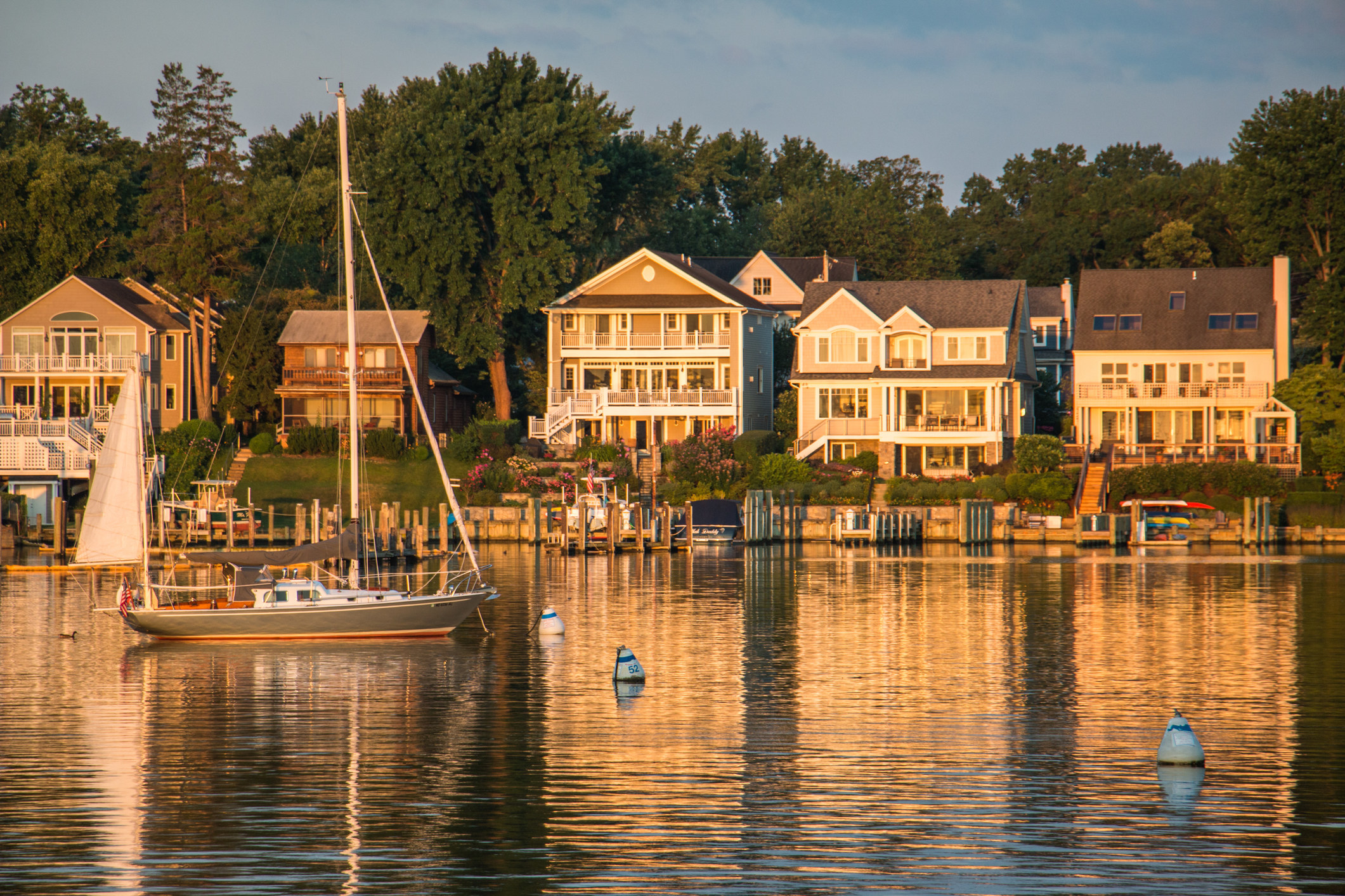 A sailboat passes by lake-front houses during golden hour in Annapolis