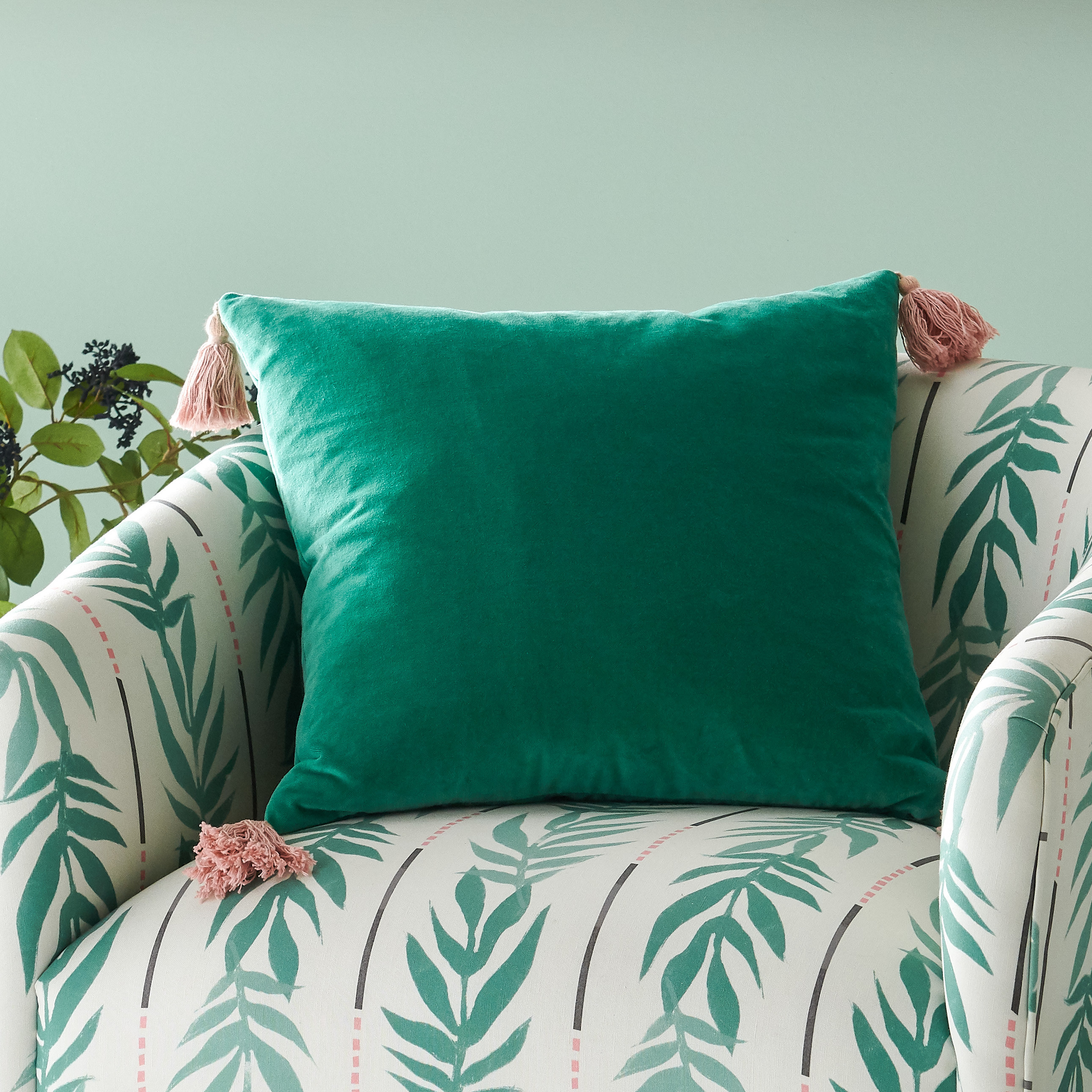 The throw pillow in green with pink tassels on a matching green printed couch