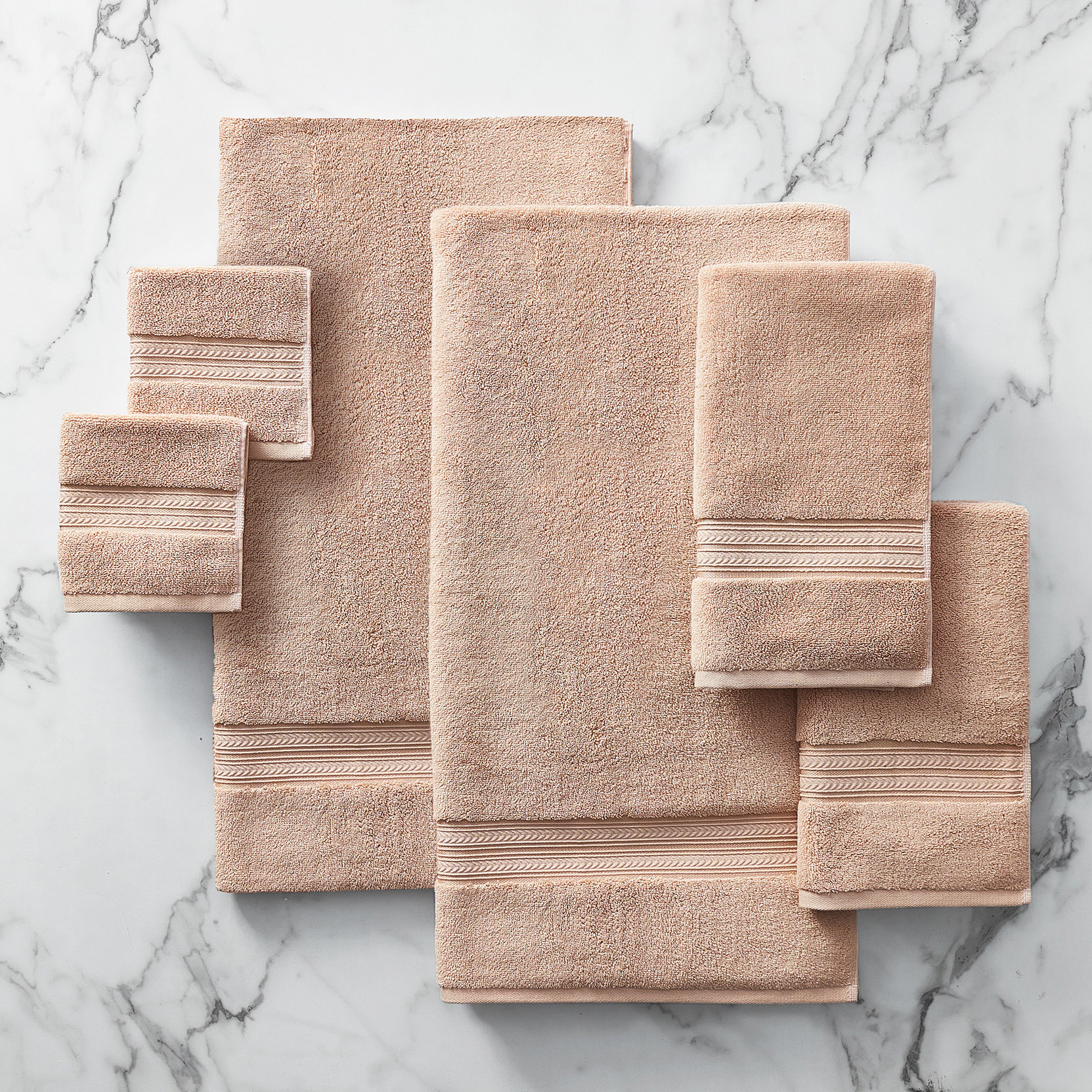 The towel set in blush pink on a marble surface