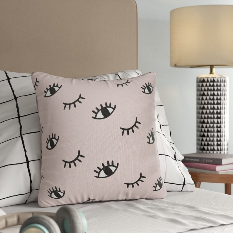 A throw pillow with little eyes with eyelashes all over it