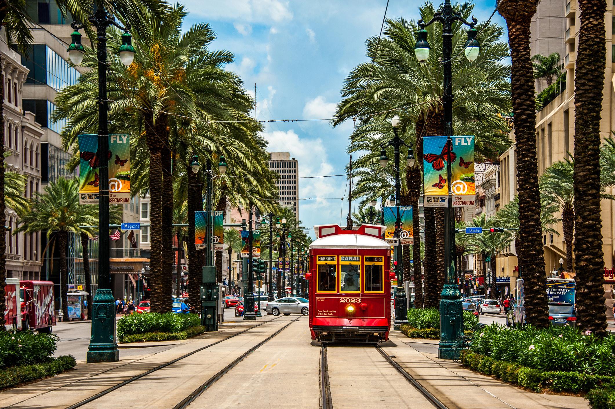 A streetcar runs down a busy street in New Orleans