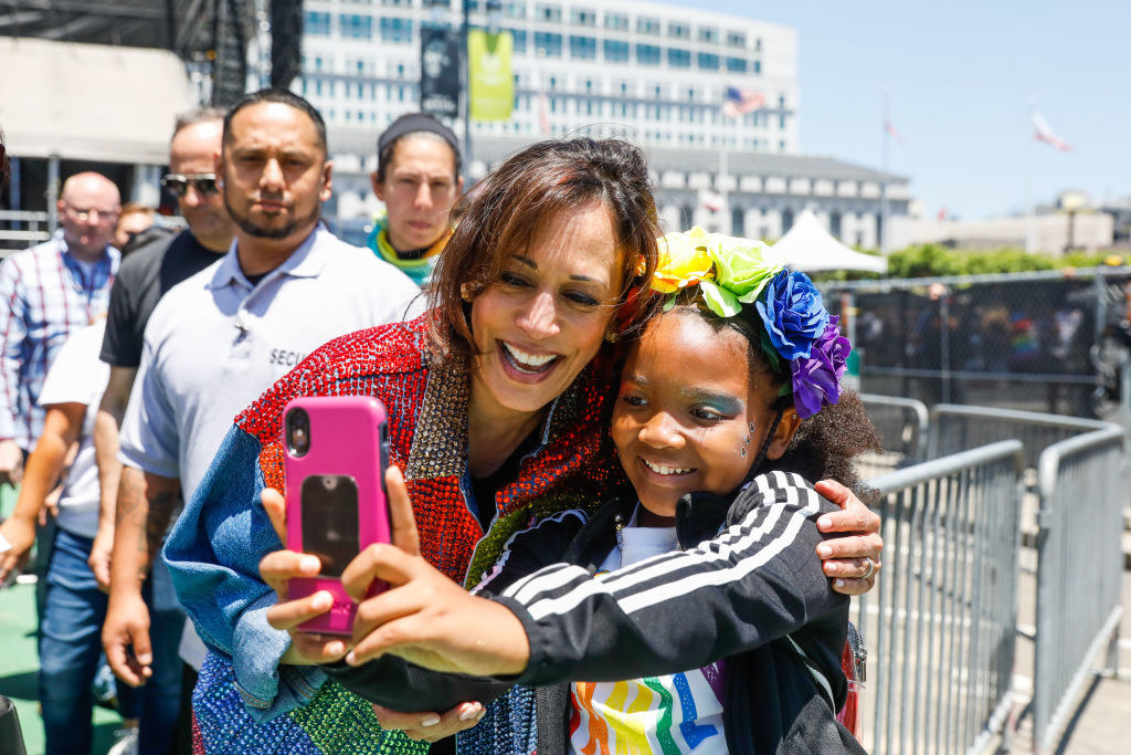 Vice President-elect Kamala Harris taking a selfie with a young girl at a Pride parade in 2019