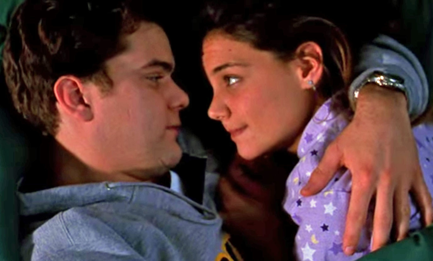 Pacey and Joey embrace while lying down and looking into each other's eyes