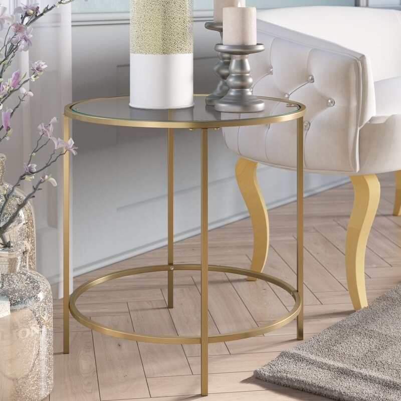 A round end table with glass top and gold frame