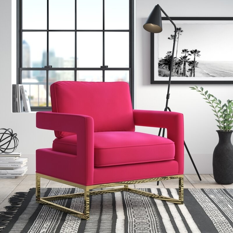 A bright pink accent chair with gold frame and legs