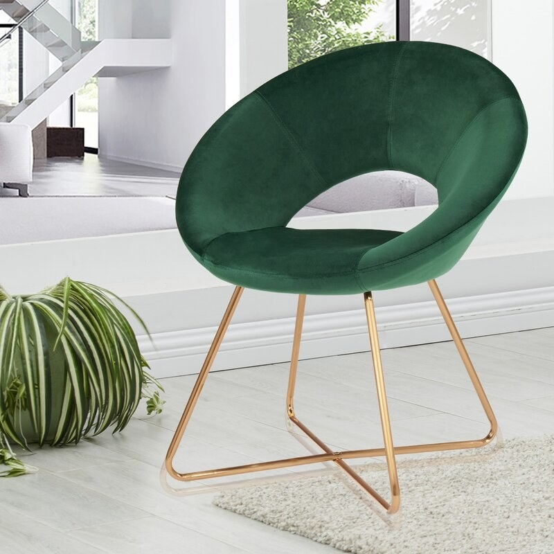 A round green velvet accent chair with gold metallic legs