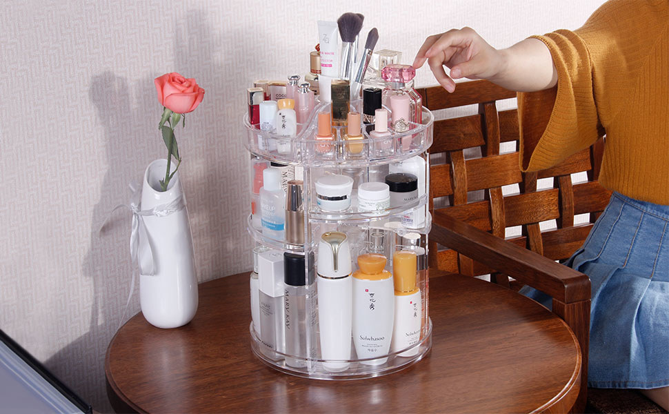 skincare product filled beauty carousel on table with person reaching towards it