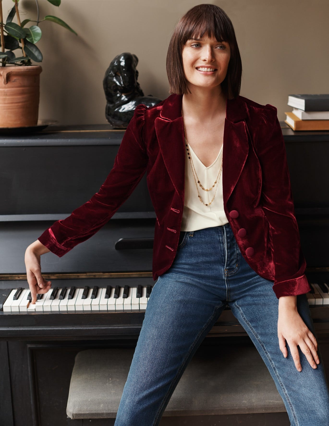 Model in a maroon velvet blazer with puff sleeves and three thick buttons