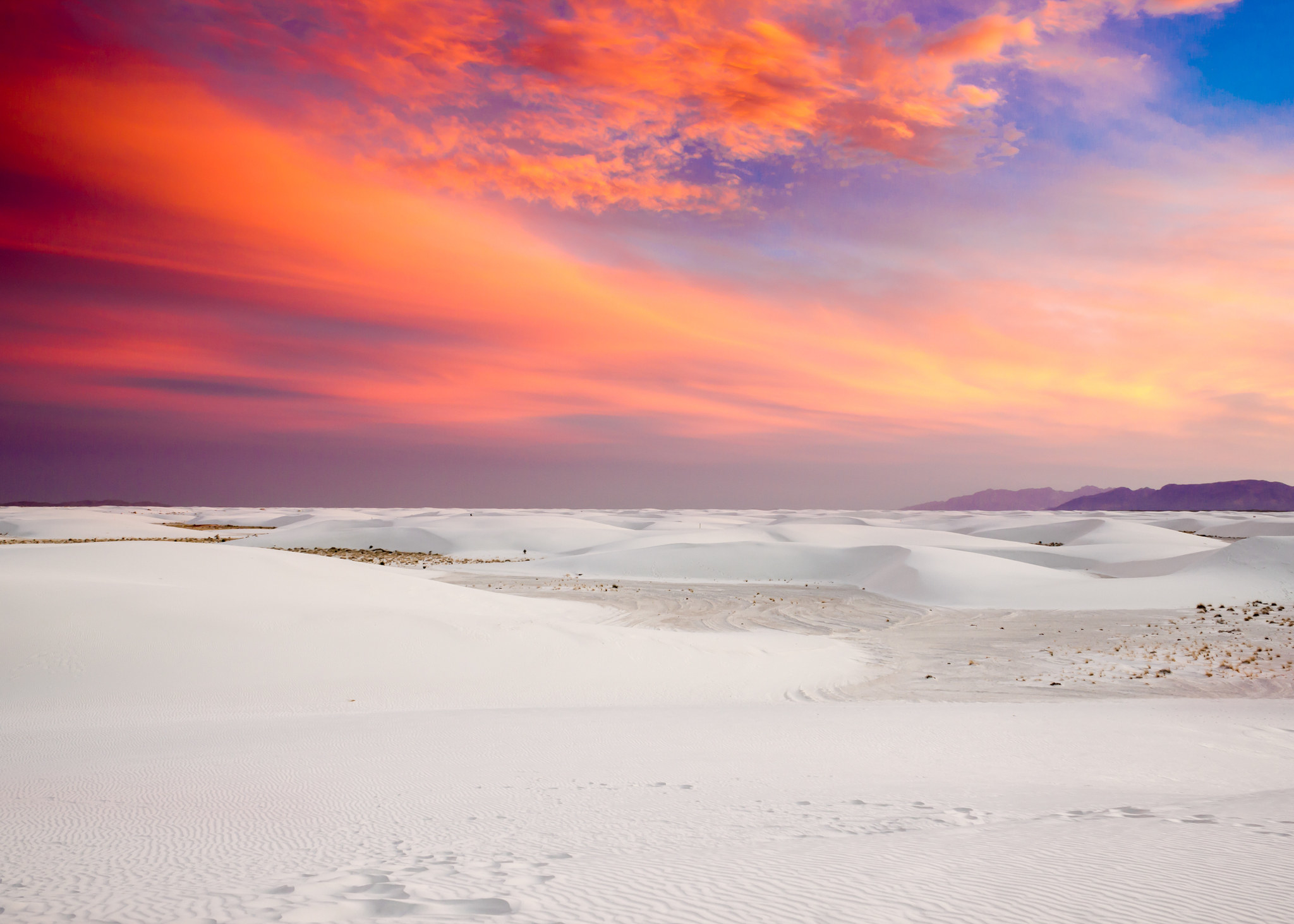 A colorful sunset over white sand desert that stretches the entire frame of the photo