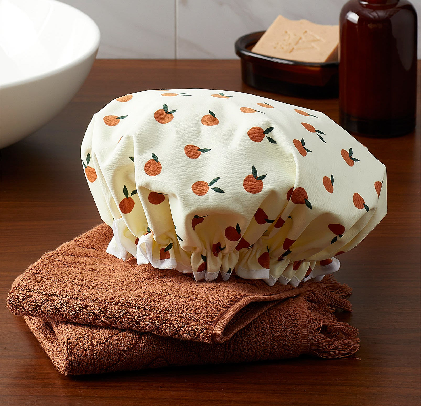 A shower cap with a fruit pattern on it lying on a folded towel