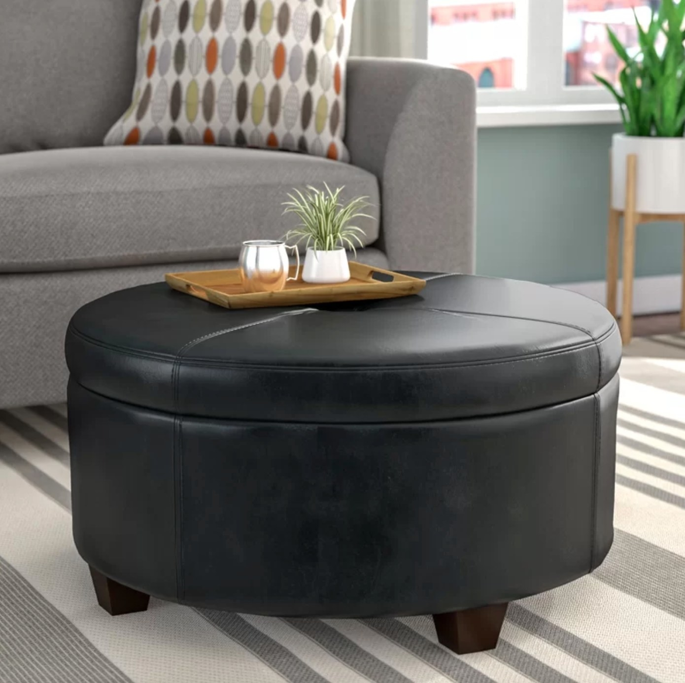 The faux leather ottoman in black