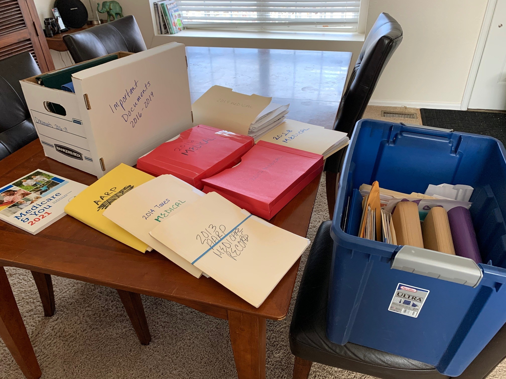 Piles of thick folders filled with medical records and labeled by year sit on a coffee table