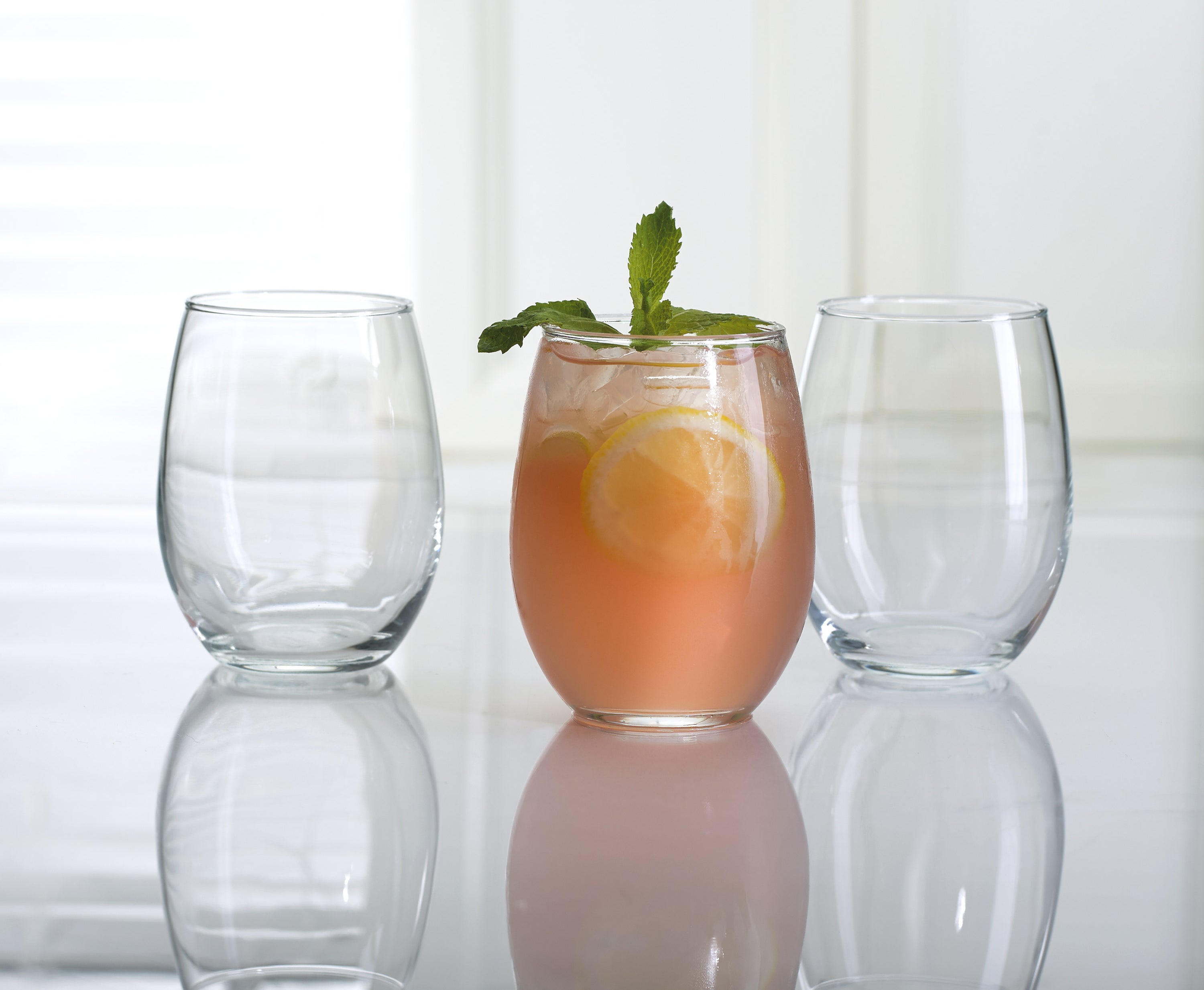 Three of the stemless wine glasses, one holding a fancy cocktail