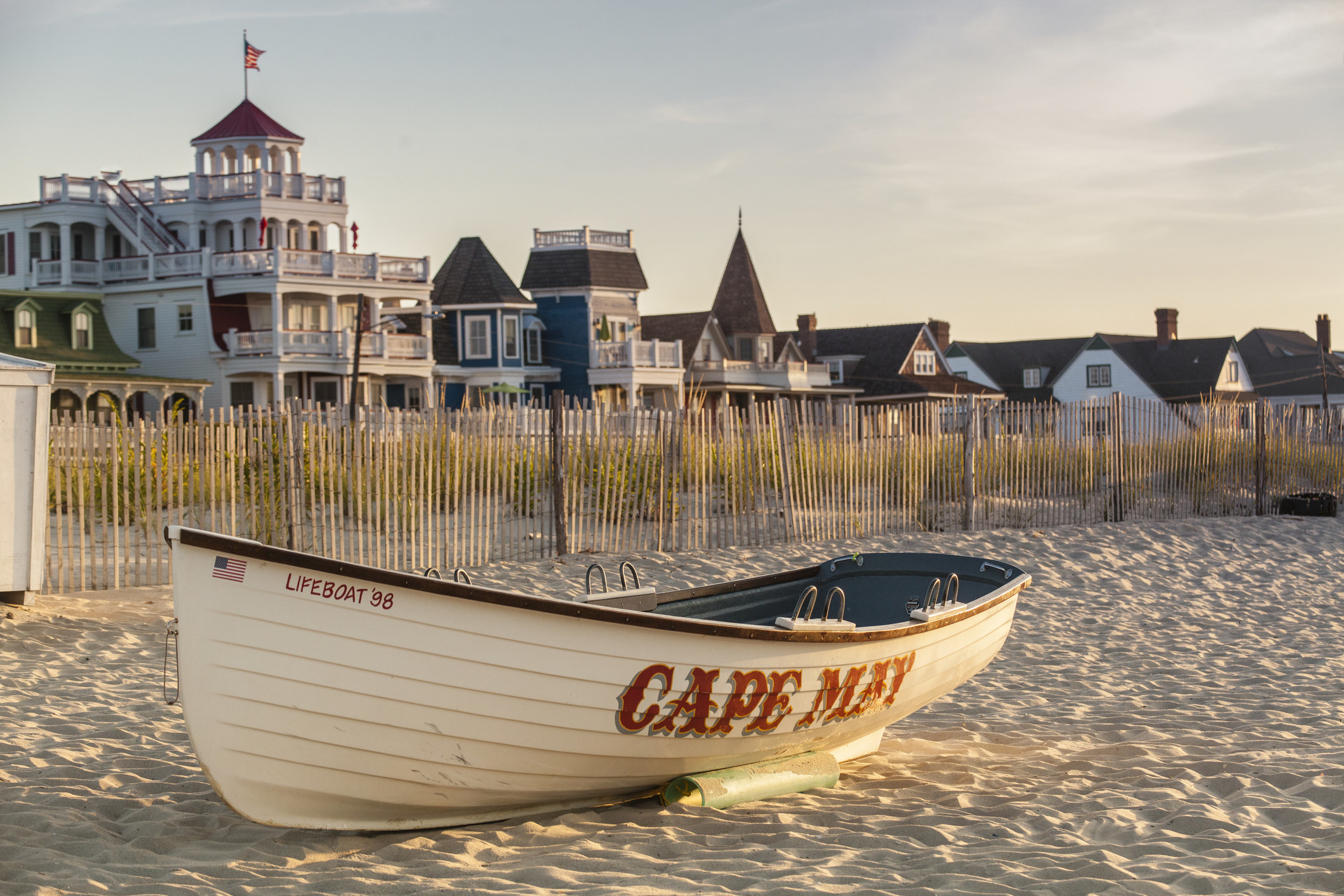 An old lifeboat sits on white sand in front of Victorian homes on Cape May
