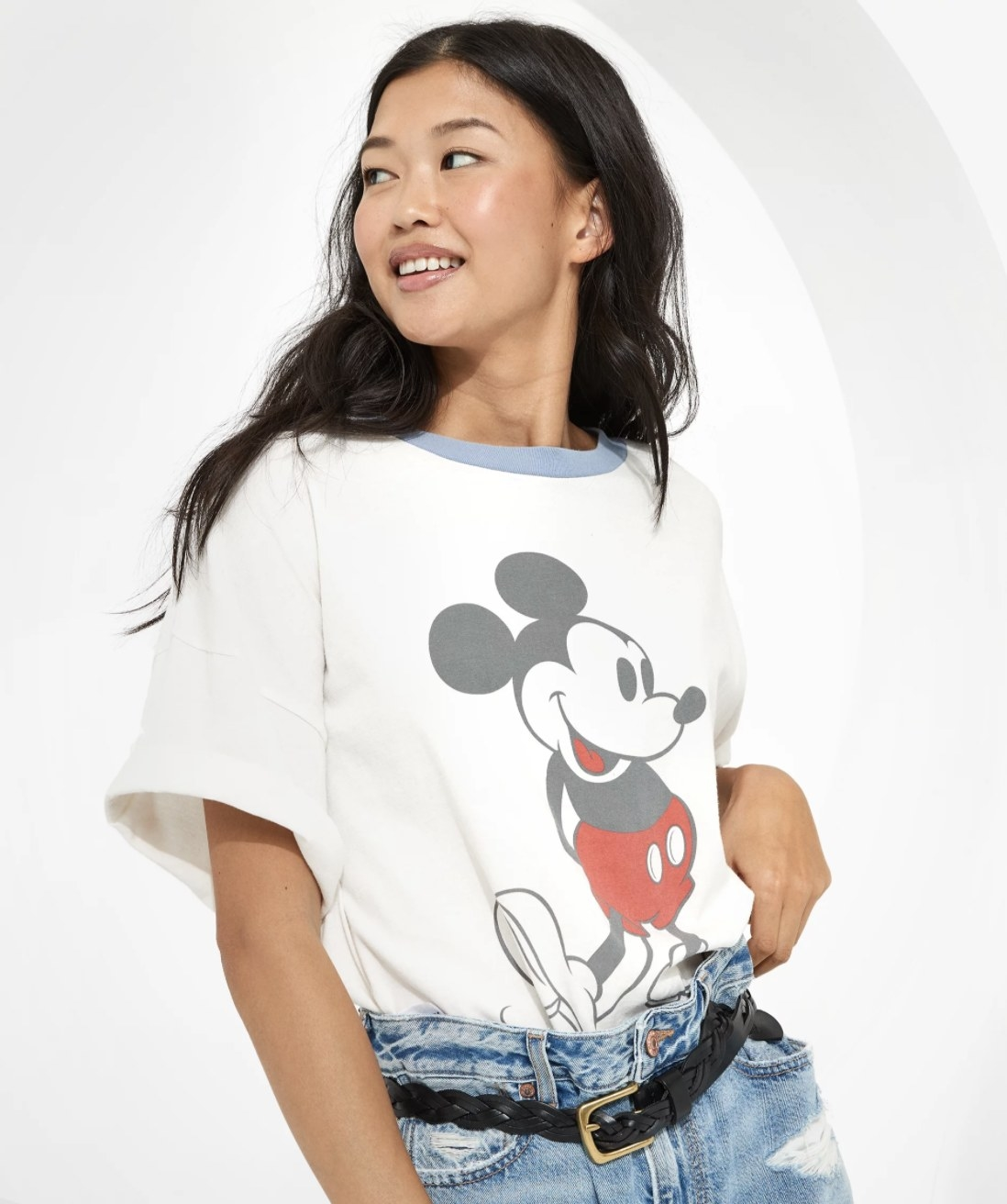 A model wears a white tee with a blue collar and a photo of Mickey Mouse