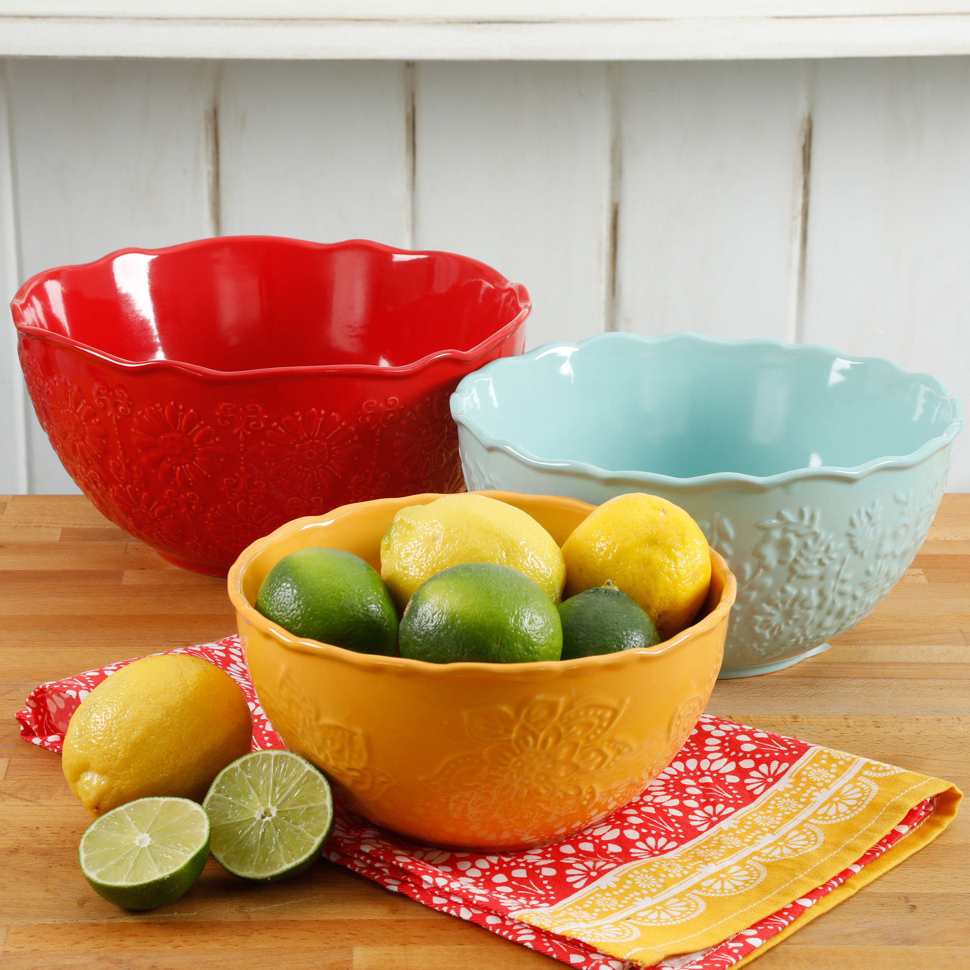 The three serving bowls in red orange and light blue, with one holding limes and lemons to show its size