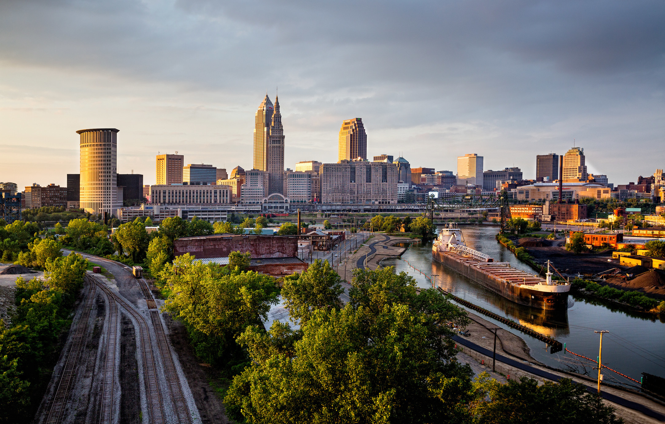 Downtown Cleveland at dusk with train tracks on the left and a freight train rolling down river on the right