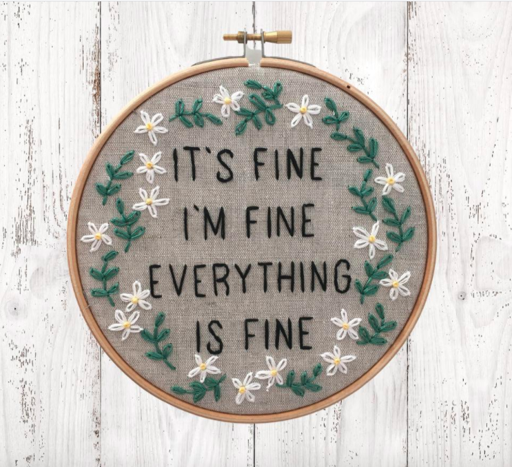 An embroidered circle with the words it's fine, i'm fine, everything is fine stitched on the front