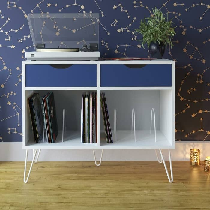White audio rack with blue drawers, a white and clear record player and a variety of records