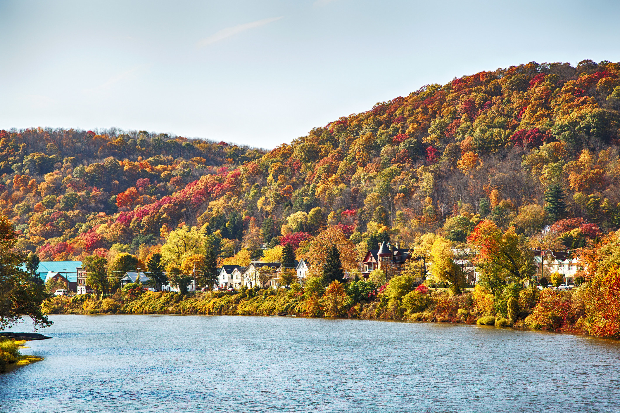 Autumn-colored trees over rolling hills with a river lined with houses in the foreground