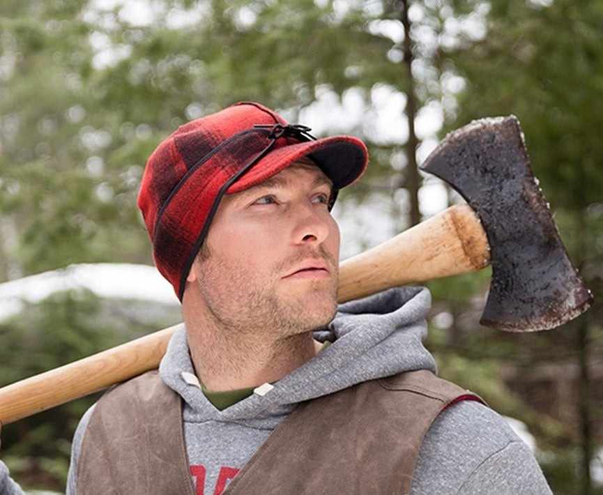 model wearing the original Stormy Kromer cap in red/black plaid while holding an ax