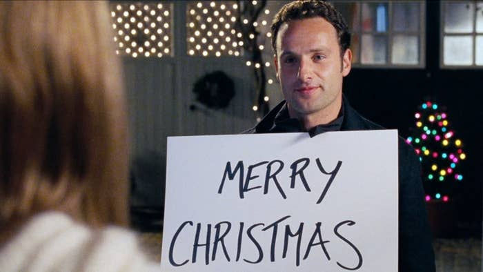 """Actor Andrew Lincoln in the movie 'Love Actually' holding up a sign that says """"Merry Christmas"""""""