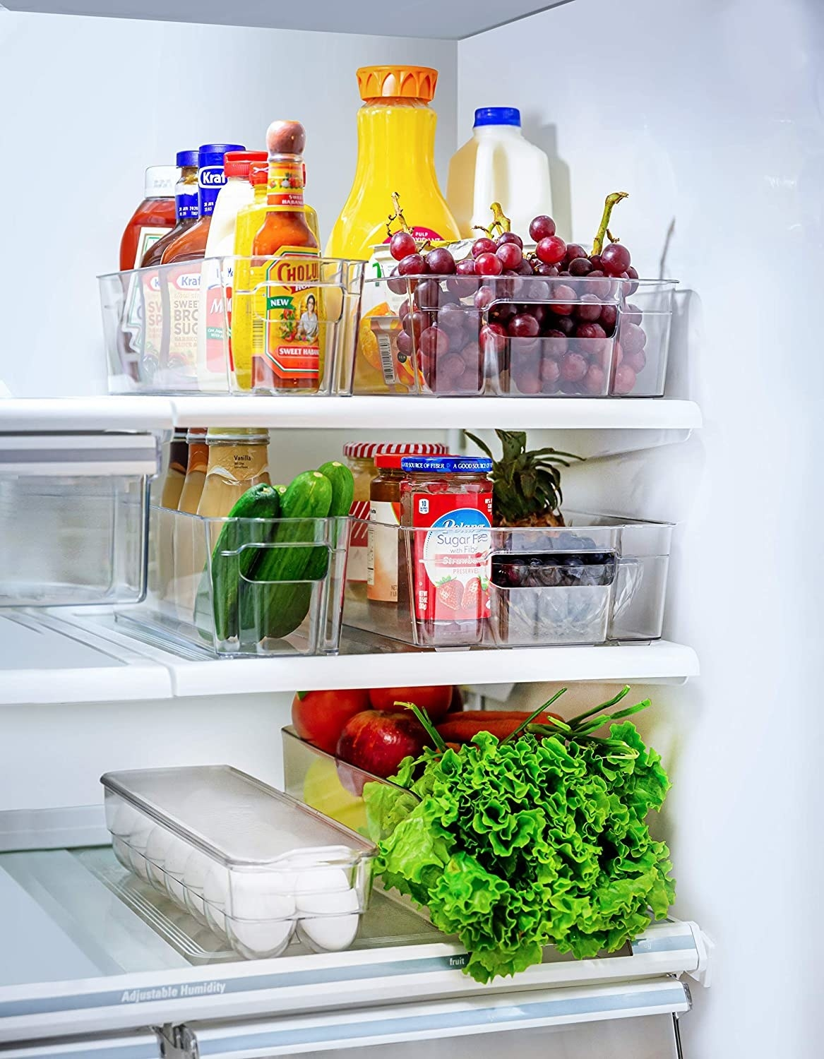produce, eggs, sauces, and juices in storage bins in the fridge