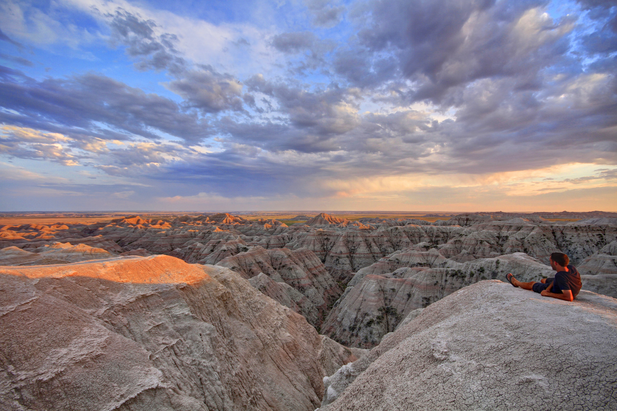 A man reclines on a rock overlooking rocky badlands during sunset
