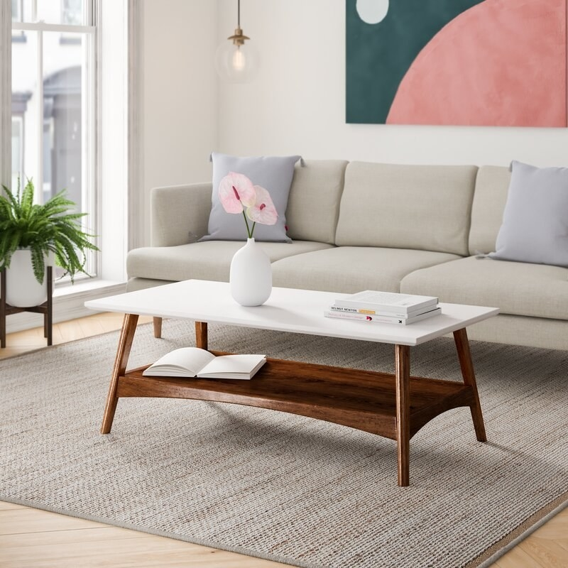 A coffee table with wooden legs and lower tier and white glossy top