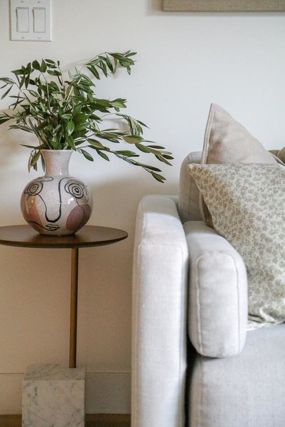A stoneware vase featuring a face pattern filled with a leafy green plant on a side table next to a couch